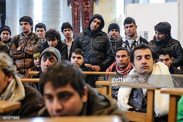 Afghan refugees listen during a press conference organized by supporters of Afghans who announced the start of a hunger strike in the Saint John the...