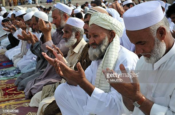 Afghan refugees offer Eid alFitr prayers near a refugee camp on the outskirts of Peshawar on August 30 2011 EidalFitr celebrations mark the end of...