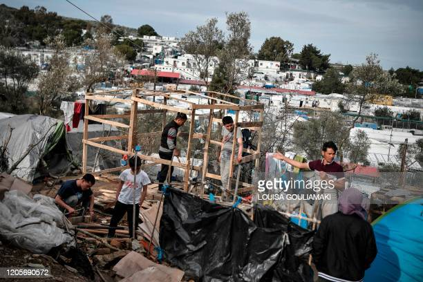 Afghan refugees set up makeshift shelter in the overcrowded Moria camp on the island of Lesbos on March 7, 2020. - Over 1,700 migrants have landed on...