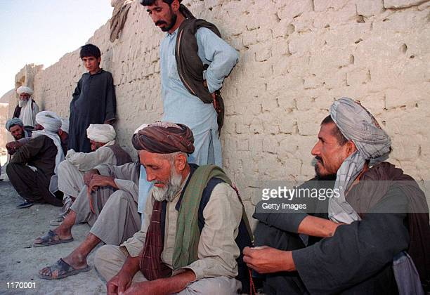 Afghan refugees take shelter from the hot sun as the allied forces bomb Afghanistan October 8 2001 in Zahedan on the border with neighboring...
