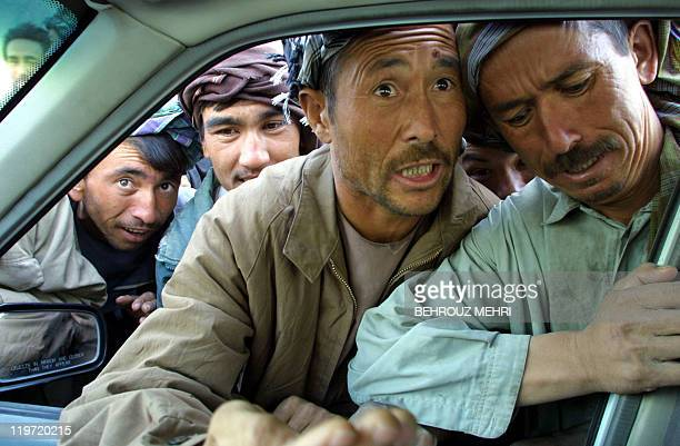 Afghan refugees try to get into a car 11 October 2001 as they are collected for menial jobs such as construction work after waiting for hours for...