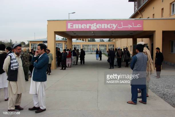 Afghan relatives of victims looks on as they stand in front of a hospital following a bomb attack in Taloqan in northeastern Takhar province on...
