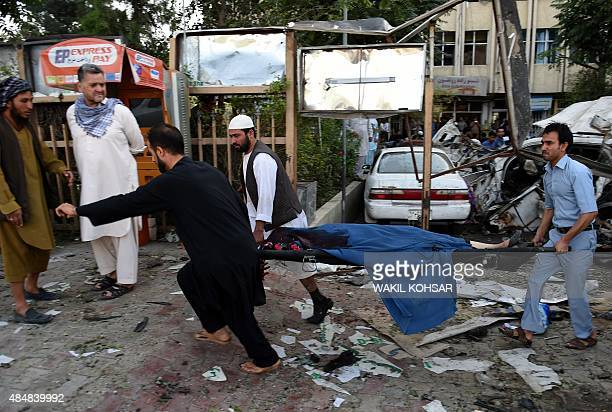 Afghan rescuers carry the body of a woman at the site of a car bomb in Kabul on August 22 2015 A suicide car bomb apparently targeting a foreign...