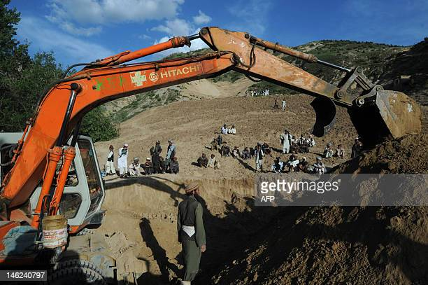 Afghan rescuers search for earthquake victims in a village at Burka district the worsthit area in the province of Baghlan north of Kabul on June 12...
