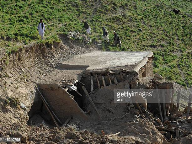 Afghan rescuers walk past the rubble of a collapsed house following an earthquake in a village at Burka district the worsthit area in the province of...