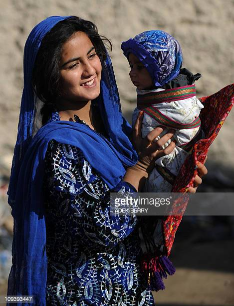 Afghan resident Nazia holds her nephew Abdul Baqi as US Marines 2nd Batallion 1st Marines Regiment members with Female Engagement Team visit her...
