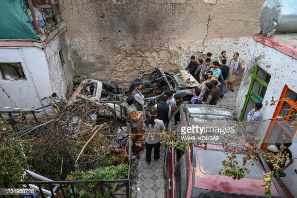 Afghan residents and family members of the victims gather next to a damaged vehicle inside a house, day after a US drone airstrike in Kabul on August...