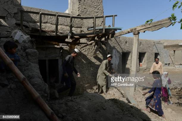 Afghan residents clear rubble from their homes after they were damaged by US airstrikes during ongoing clashes with Islamic State militants in the...