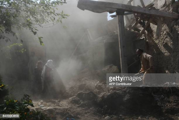 TOPSHOT Afghan residents clear rubble from their homes after they were damaged by US airstrikes during ongoing clashes with Islamic State militants...