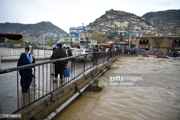Afghan residents cross a bridge after heavy rains along the Kabul river in Kabul on April 16 2019 Torrential rainstorms have lashed droughtstricken...