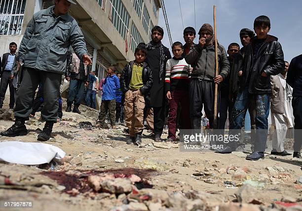 Afghan residents gather at the scene of a roadside bomb explosion at Khair Khana in Kabul on March 29 2016 A roadside bomb attack in a residential...