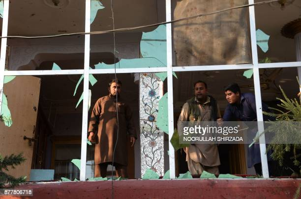 Afghan residents inspect damages on a building near the site of suicide attack in Jalalabad on November 23 2017 A suicide bomber struck at a crowd of...