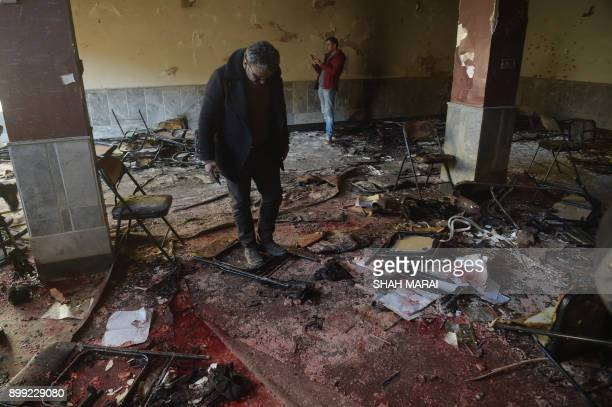Afghan residents inspect the site of a bomb attack on a Shiite cultural centre in Kabul on December 28 2017 At least 40 people were killed and dozens...