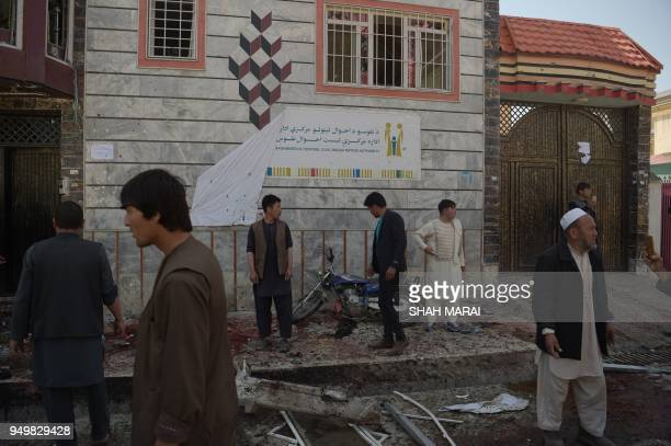TOPSHOT Afghan residents inspect the site of a suicide bombing outside a voter registration centre in Kabul on April 22 2018 A suicide bomber blew...