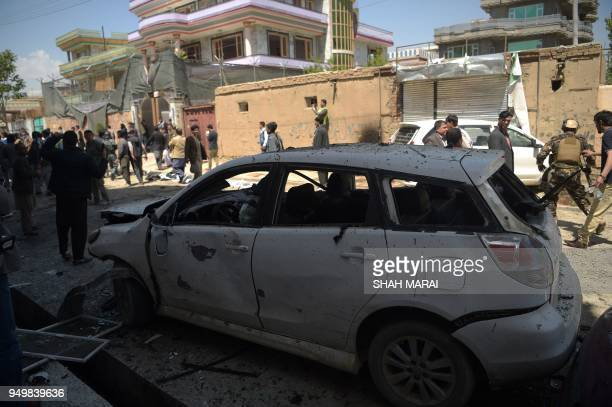 Afghan residents inspect the site of a suicide bombing outside a voter registration centre in Kabul on April 22 2018 A suicide bomber blew himself up...