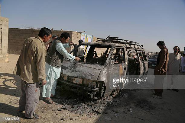 Afghan residents inspect the wreckage of a burnt out car which carried a Taliban suicide attacker in Ghazni on August 29 2013 Taliban attacks across...