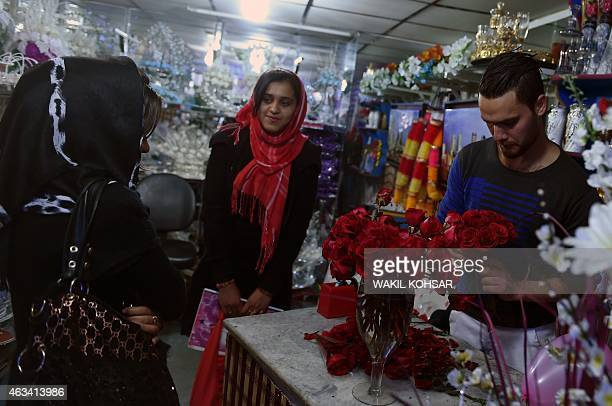 Afghan residents Khujesta and Sama Sadat shop for flowers as gifts to celebrate Valentine's Day in the ShareNaw area of Kabul on February 14 2015 In...