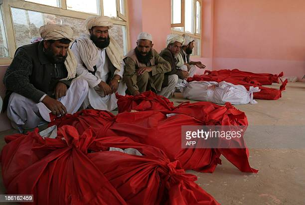 Afghan residents look at the victims of a roadside bomb in the Andar district of the Ghazni province on October 28 2013 A roadside bomb on October 27...