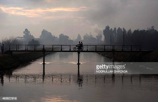 Afghan residents ride on a motorbike across a bridge on the outskirts of Jalalabad in Nangarhar province on February 20 2015 AFP PHOTO / Noorullah...