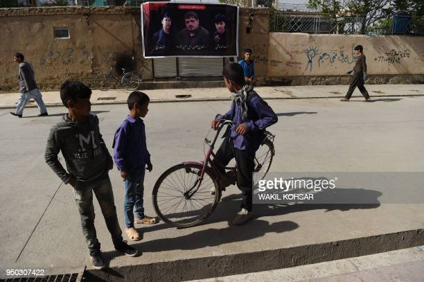 Afghan residents stand along a street near a banner with the image of Wakil Hussain Allahdad one of the 57 victims of a bomb blast a day after the...