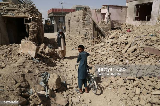 Afghan residents walk near destroyed houses after a Taliban attack in Ghazni on August 16, 2018. - Afghan forces appeared to have finally pushed...