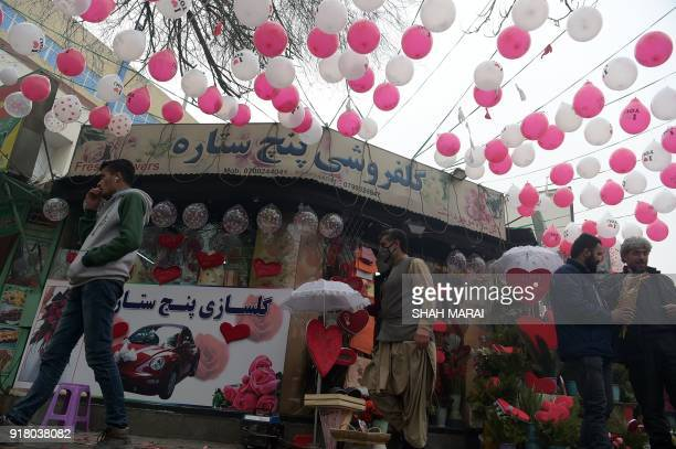 Afghan residents walk past a shop selling gifts to celebrate Valentine's Day in Kabul on February 14 2018 In conservative Afghanistan many Afghans...