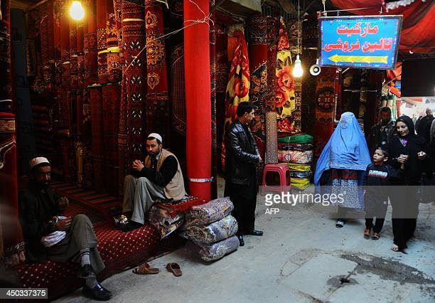 Afghan residents walk through a market in Kabul on November 18 2013 Some nine million Afghans or 36 percent of the population are living in absolute...