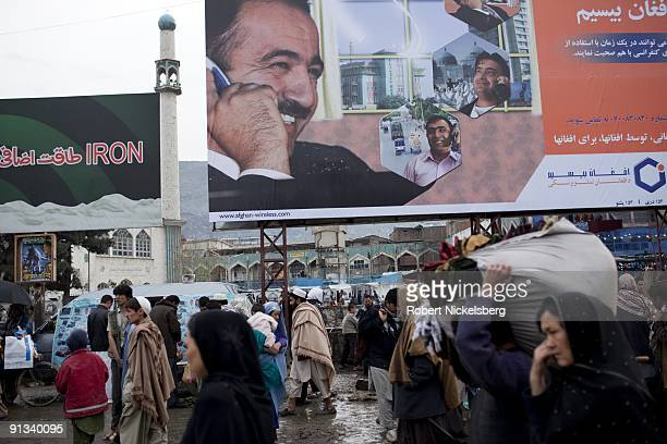 Afghan residents walk under a mobile phone billboard ad along the Kabul River market area April 6 2009 Kabul Afghanistan Kabul has an estimated...