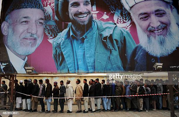 Afghan residents wishing to vote line up underneath a billboard showing images of Afghan President Hamid Karzai and of deceased Afghan figures...