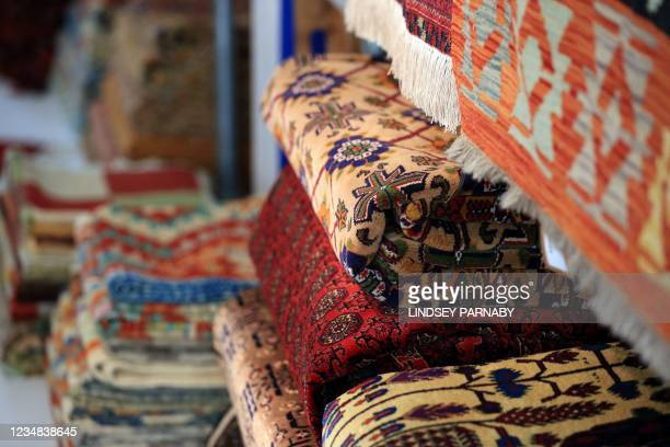 Afghan rugs are arranged for sale at The Afghan Rug Shop in Hebden Bridge, northern England, on August 20, 2021. - Overseas businesses selling...