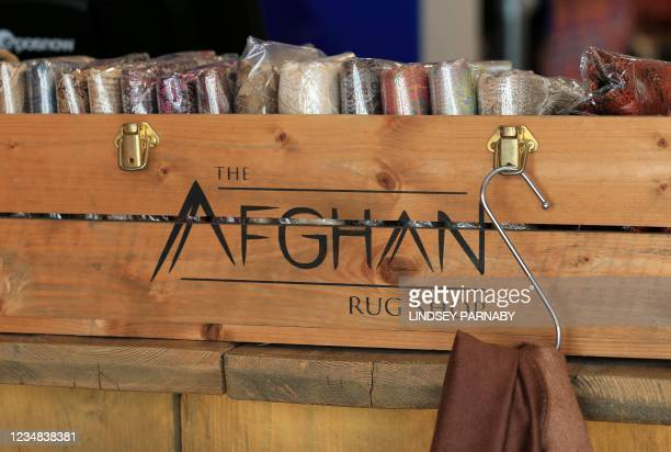 Afghan scarves are arranged for sale at The Afghan Rug Shop in Hebden Bridge, northern England, on August 20, 2021. - Overseas businesses selling...