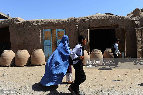 Afghan schollboys and a woman walk past a traditional oven factory in Herat on May 20 2013 Some nine million Afghans or 36 percent of the population...