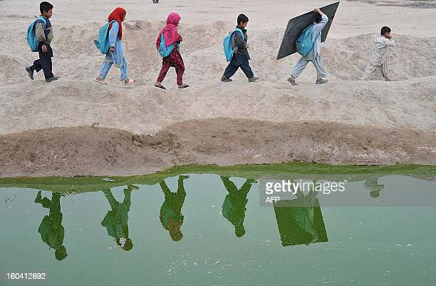 Afghan school children walk home after classes near an open classroom in the outskirts of Jalalabad on January 30 2013 Afghanistan has had only rare...