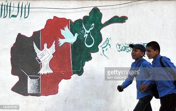 Afghan schoolboys walk past a mural of painted with the colours of the Afghan national flag in Kabul on May 21 2012 NATO leaders endorsed on May 21...