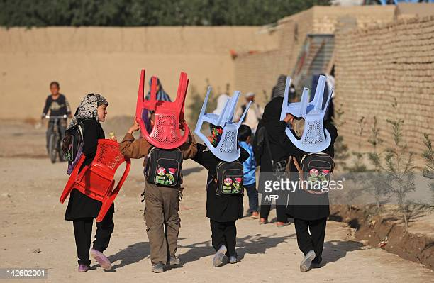 Afghan schoolchildren carry their chairs to a class in an open area in Mazar-i Sharif, capital of the Balkh province on April 9, 2012. At the start...