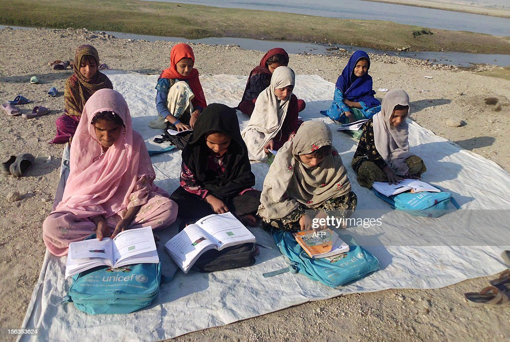 Afghan schoolgirls study at an outdoor classroom in the rural districts of Laghman province on November 13, 2012. Afghanistan has had only rare moments of peace over the past 30 years, its education system being undermined by the Soviet invasion of 1979, a civil war in the 1990s and five years of Taliban rule. AFP PHOTO/ Waseem Nikzad
