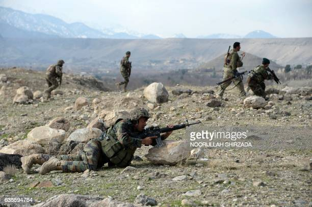 Afghan security force personnel look on during an ongoing an operation against Islamic State militants in Kot district of Nangarhar province on...
