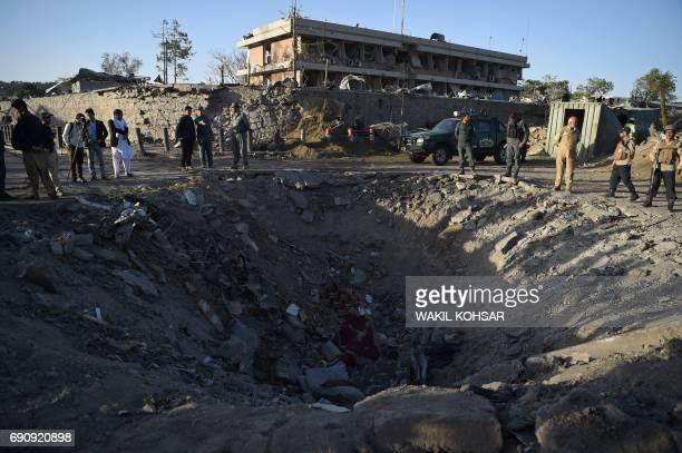 Afghan security forces and residents stand near the crater left by a truck bomb attack in Kabul on May 31 2017 At least 80 people were killed and...