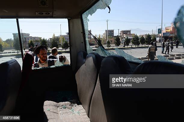 Afghan security forces are seen through the shattered glass of a bus at the scene of the roadside bomb blast in Kabul on November 10 2014 Two Taliban...