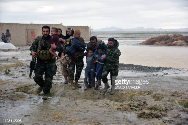 Afghan Security forces carry children after flood affected their homes in Arghandab district of Kandahar province on March 2 2019 At least 20 people...
