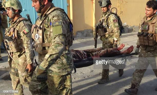 Afghan security forces carry the body of a victim from the site of an attack in Jalalabad on July 28 2018 An hourslong militant attack on a midwife...