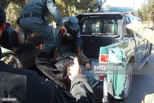 Afghan security forces carry wounded soldier after suspected Taliban suicide bombers and gunmen attacked a bank in the Helmand province of...