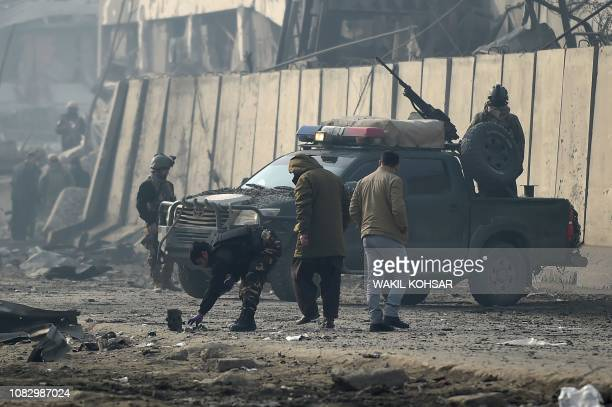 Afghan security forces gather at the site of a powerful truck bomb attack a day after it detonated near a foreign compound in Kabul on January 15...