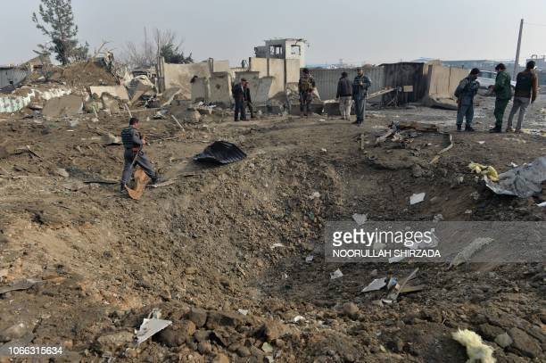 Afghan security forces gather at the site of a suicide bomb attack outside a British security firm's compound in Kabul, a day after the blast on...