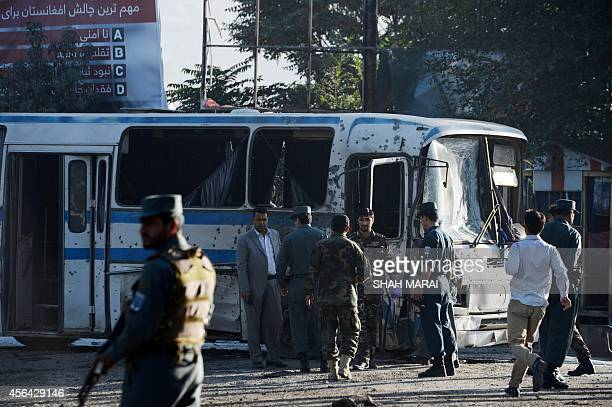 Afghan security forces inspect near an army bus at the site of a suicide attack in Kabul on October 1 2014 Two Taliban suicide bombers hit army buses...
