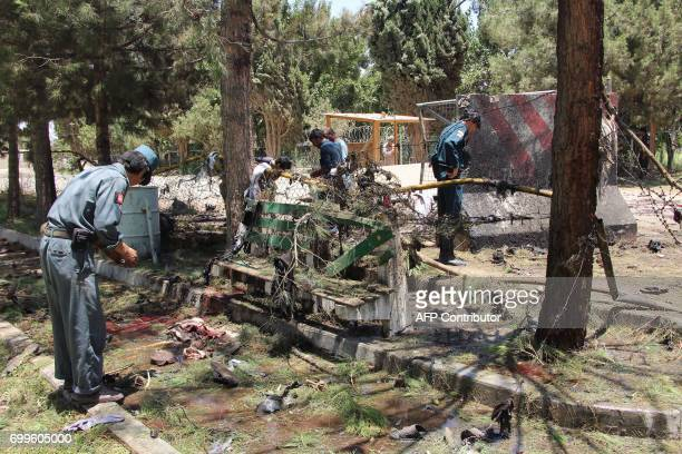 Afghan security forces inspect the site of a powerful car bomb in Lashkar Gah the capital of Helmand province on June 22 2017 Twenty people were...