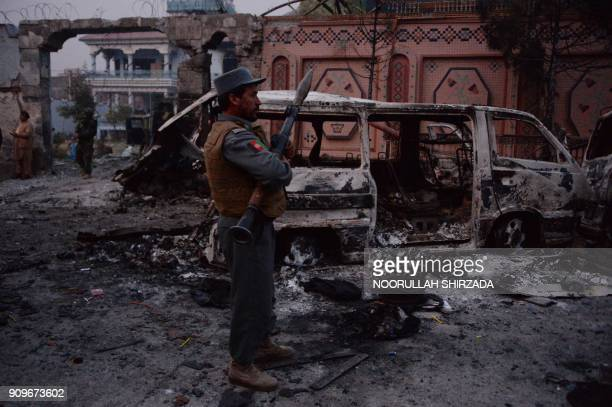 TOPSHOT Afghan security forces inspect the site of attack on British charity Save the Children office in Jalalabad on January 24 2018 Save the...
