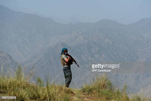 Afghan security forces keep watch near the site of US airstrike on a civilian vehicle in Haska Mina district Nangarhar province on August 12 2017 The...