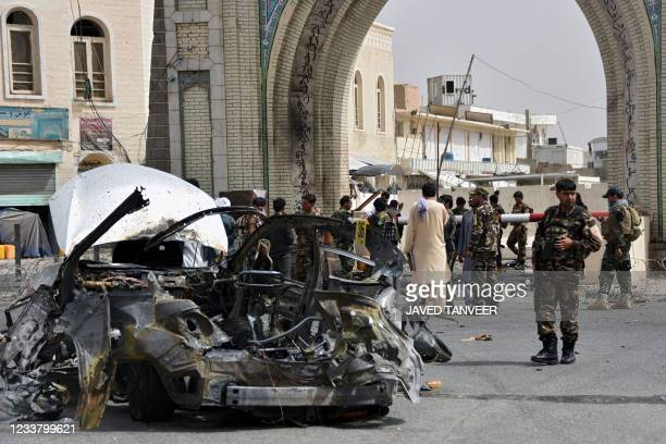 Afghan security forces personnel inspect the remains of a vehicle at the site of a bomb blast in Kandahar on July 4, 2021.