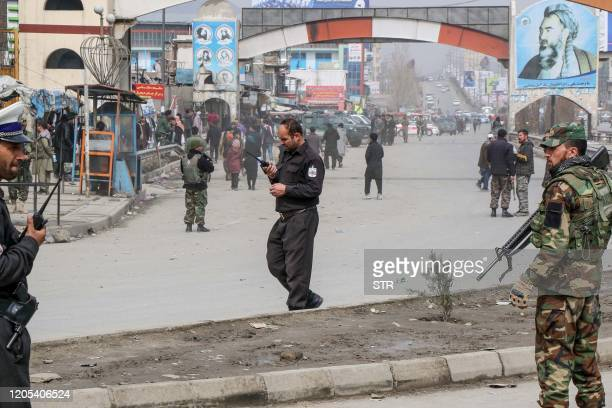 Afghan security forces personnel stand guard on a road near the site of a gun attack that occured during an event ceremony to mark the 25th...